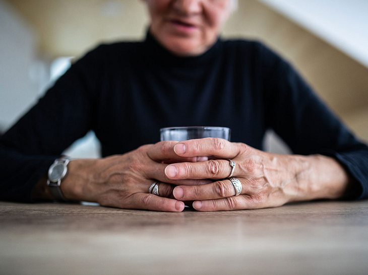 Ältere Dame hält sich an einem Glas Alkohol fest