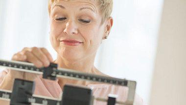 Abnehmen in den Wechseljahren: Eine Frau vor einer Waage