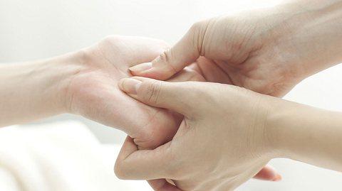 Frau drückt bei einer anderen Frau Akupressurpunkte an der Hand.
