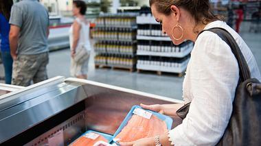 Eine Frau sucht im Supermarkt nach passendem Fleisch. - Foto: iStock / Juanmonino