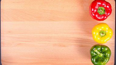 Eine rote, eine gelbe und eine grüne Paprika auf einem Holzbrett.
