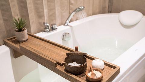 Badewannenablage aus Holz auf gefüllter Badewanne - Foto: iStock/Panupong Piewkleng