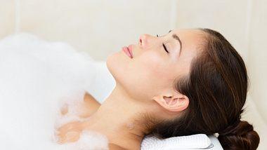 Frau in gefüllter Badewanne mit Badewannenkissen - Foto: iStock/ariwasabi