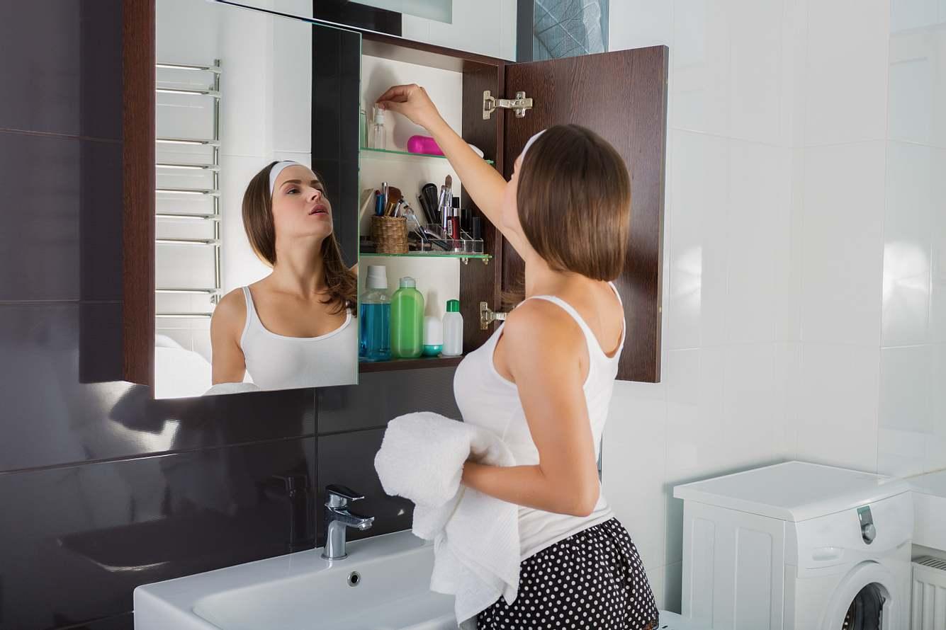 Frau nimmt Kosmetik aus einem Badezimmerschrank heraus