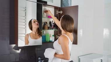 Frau nimmt Kosmetik aus einem Badezimmerschrank heraus - Foto: iStock/Tinatin1