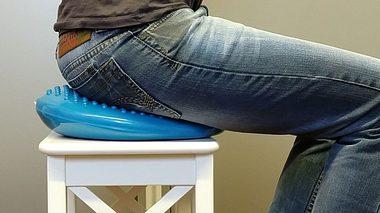 Mann sitzt auf einem Balancekissen