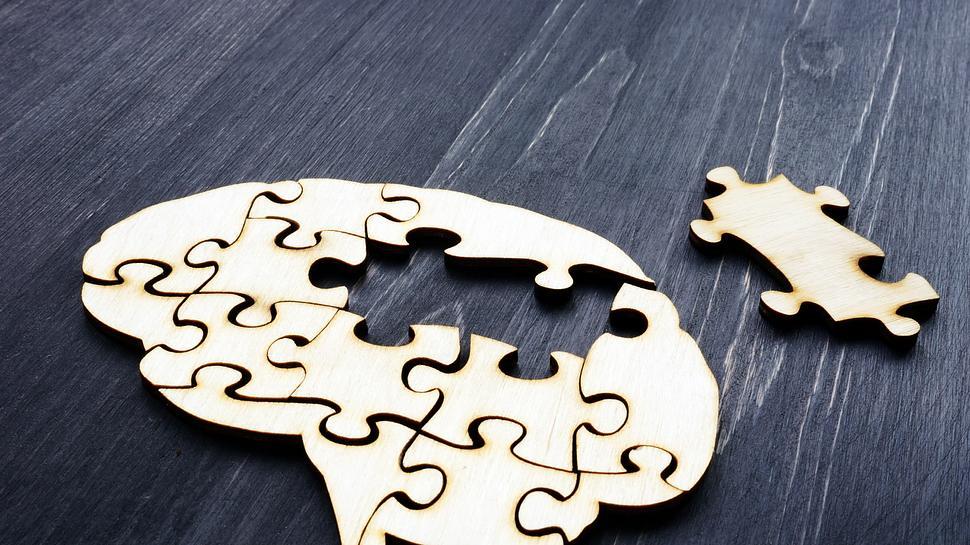 Holzpuzzle, das aussieht wie ein Gehirn dem Teile fehlen.  - Foto: designer491 / iStock