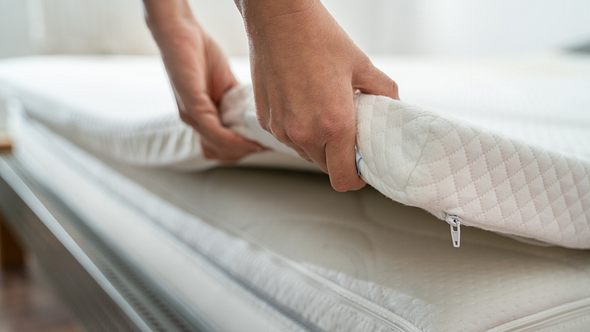Mensch wechselt Bett Topper - Foto: iStock/AndreyPopov