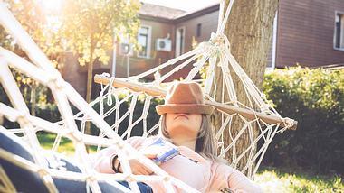 Eine Frau genießt die Sonne in der Hängematte. - Foto: iStock / Enes Evren