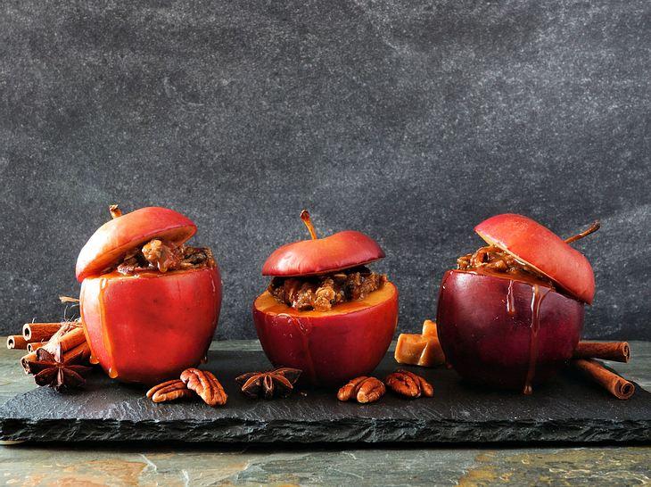 Drei Bratäpfel mit Zimtstangen und Walnüssen auf einer Schieferplatte