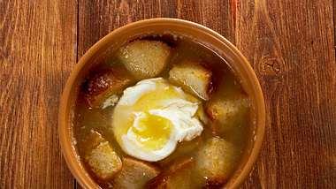 Die Sopa de ajo ist eine klassische Knoblauch-Brot-Suppe mit pochiertem Ei. - Foto: MychkoAlezander / iStock