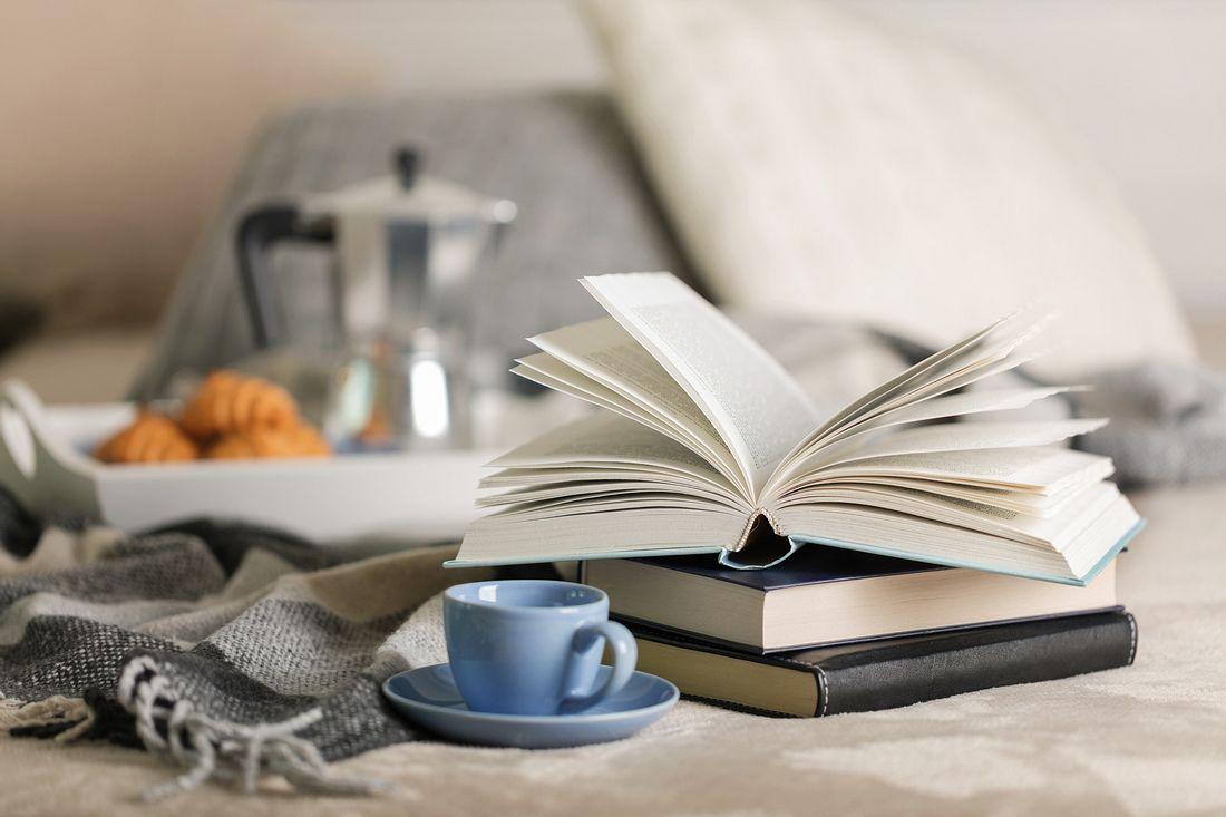 Bücher und Kaffeetasse auf Bett