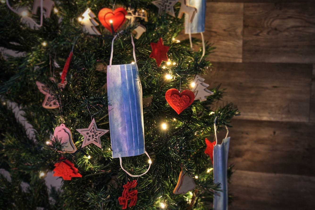 Ein Weihnachtsbaum mit weihnachtlicher Dekoration und Corona-Schutzmasken geschmückt.