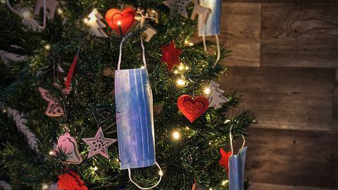 Ein Weihnachtsbaum mit weihnachtlicher Dekoration und Corona-Schutzmasken geschmückt. - Foto: Margarita Monge Ortega / iStock