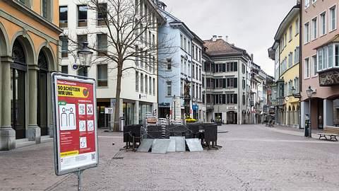In einer leeren Einkaufsstraße steht ein Schild mit Corona-Schutzmaßnahmen.  - Foto: yuelan / iStock