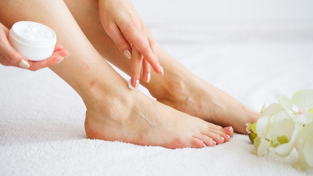 Frau nutzt Creme für trockene Füße - Foto: iStock/Iurii Maksymiv