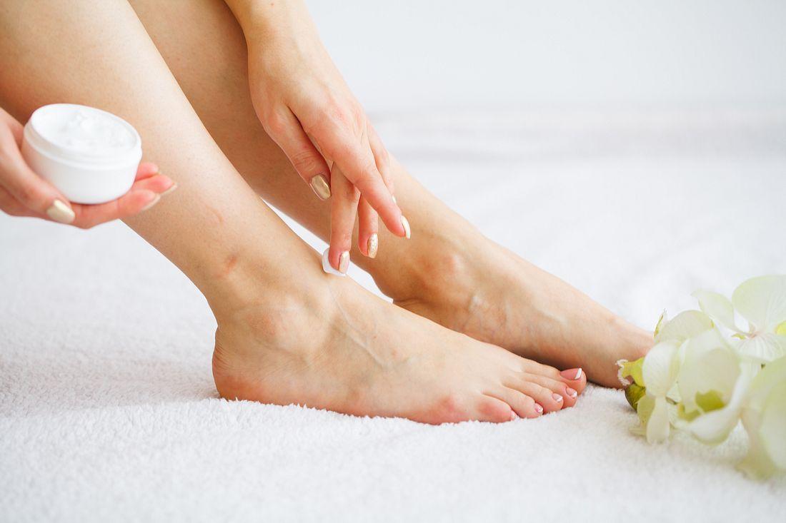 Frau nutzt Creme für trockene Füße