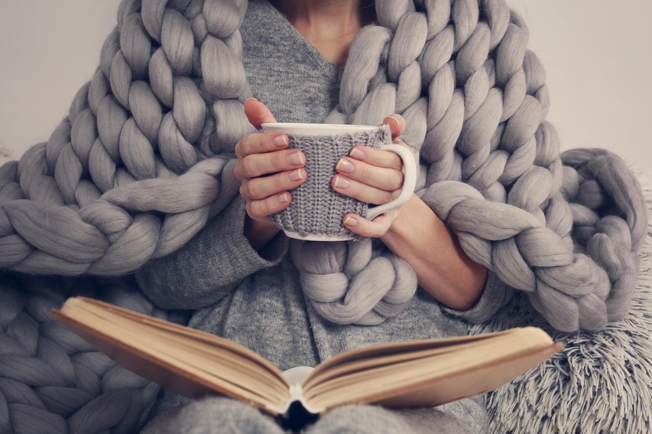 Frau trinkt Tee, liest und ist mit einer Decke zugedeckt.