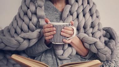 Frau trinkt Tee, liest und ist mit einer Decke zugedeckt. - Foto: iStock/Albina Gavrilovic