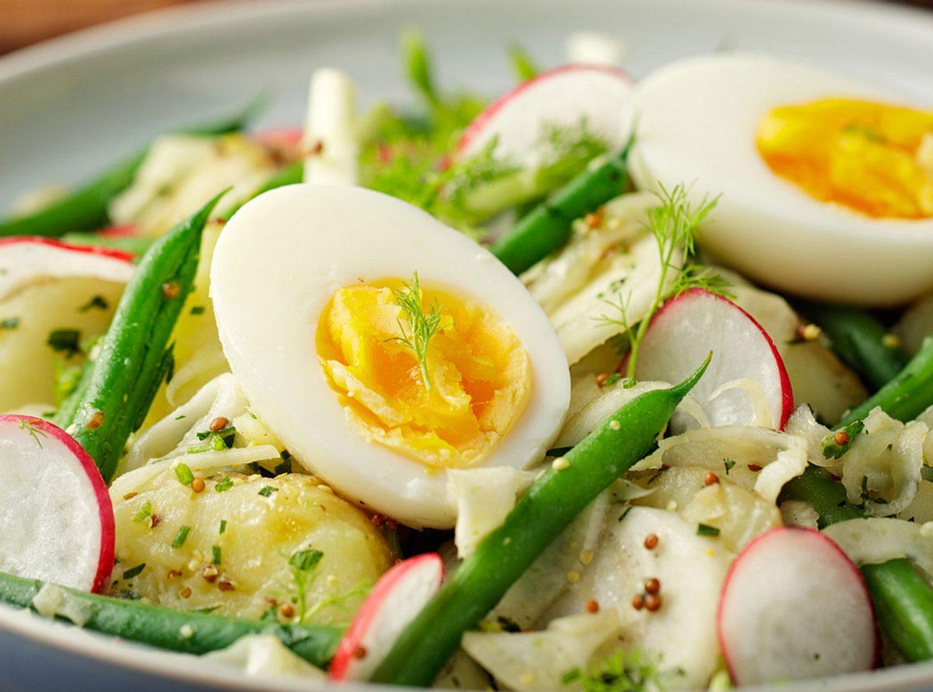 Gekochte Eier mit gekochten Kartoffeln, dekoriert mit grünen Bohnen und Radieschen.