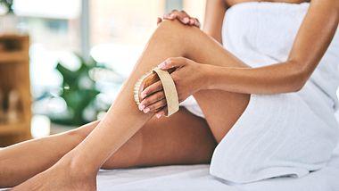 Frau peelt Beine gegen eingewachsene Haare - Foto: iStock/Moyo Studio