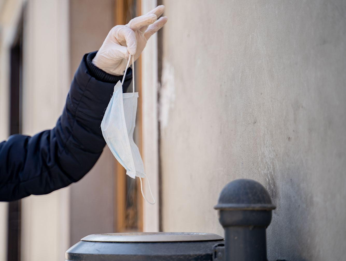 Frau wirft Einwegmaske in öffentlichen Mülleimer.