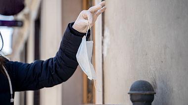 Frau wirft Einwegmaske in öffentlichen Mülleimer.  - Foto: CasarsaGuru / iStock