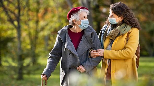 Zwei Damen gehen mit OP-Maske im Park spazieren. - Foto: iStock / Ridofranz