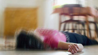 Frau liegt nach epileptischen Anfall auf dem Boden ihrer Küche.  - Foto: Tunatura / iStock