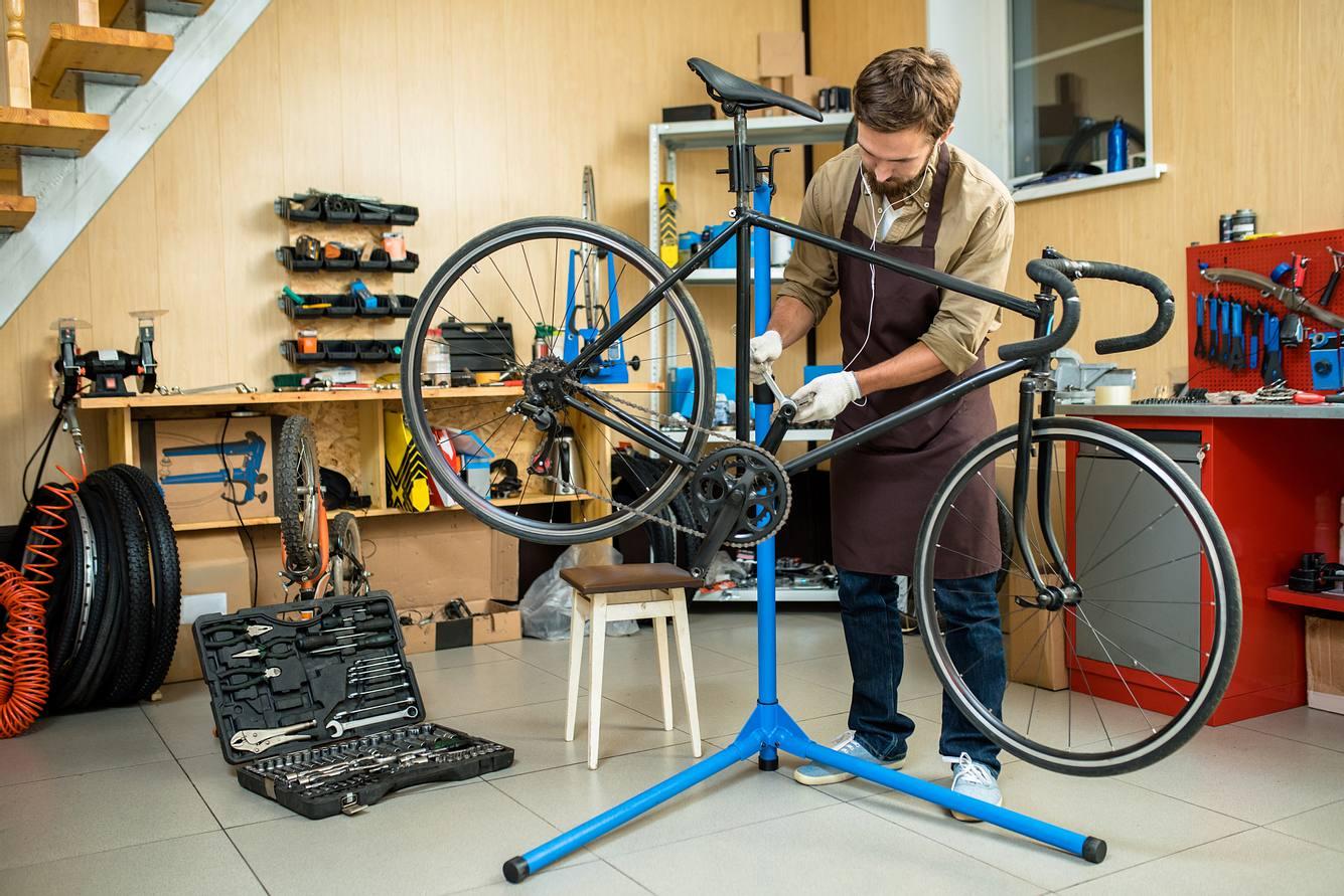 Mann repariert Fahhrad auf einem Fahrrad-Montageständer.
