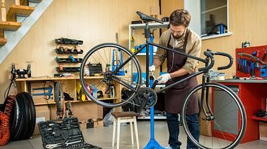 Mann repariert Fahhrad auf einem Fahrrad-Montageständer. - Foto: iStock/ shironosov