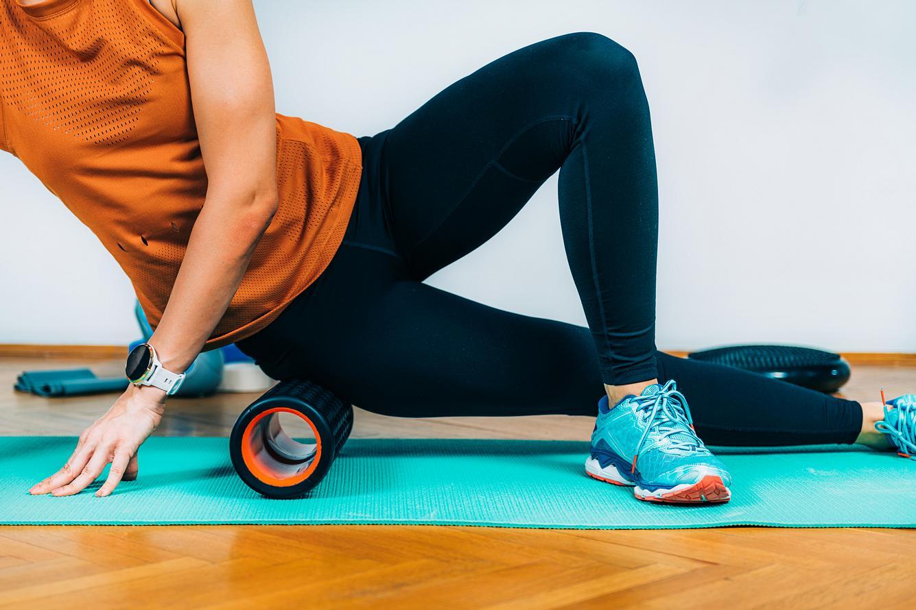 Frau macht Übungen mit einer Faszienrolle.