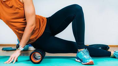 Frau macht Übungen mit einer Faszienrolle. - Foto: iStock/ microgen