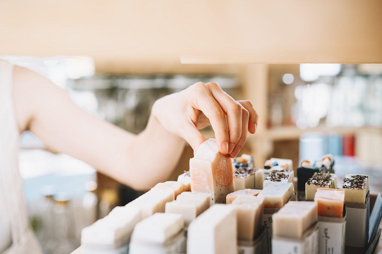 Frauenhand greift festes Shampoo im Regal