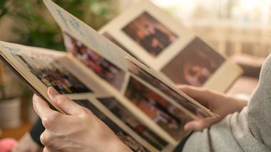 Frau blättert in Fotoalbum - Foto: iStock/Olga Ihnatsyeva