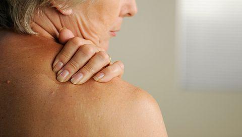 Frau greift sich an schmerzende Schulter.  - Foto: peepo / iStock