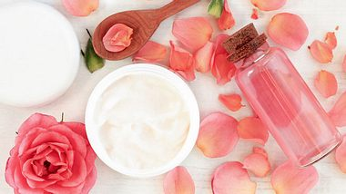 Flasche mit Rosenöl auf Blütenblättern