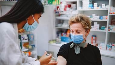 Eine Frau mit Mundschutz wird geimpft.  - Foto: iStock / lechatnoir