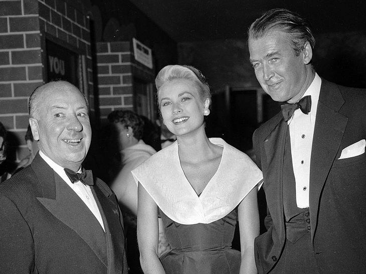 Grace Kelly, Alfred Hitchcock und James Stewart bei der Premiere des Films Das Fenster zum Hof.