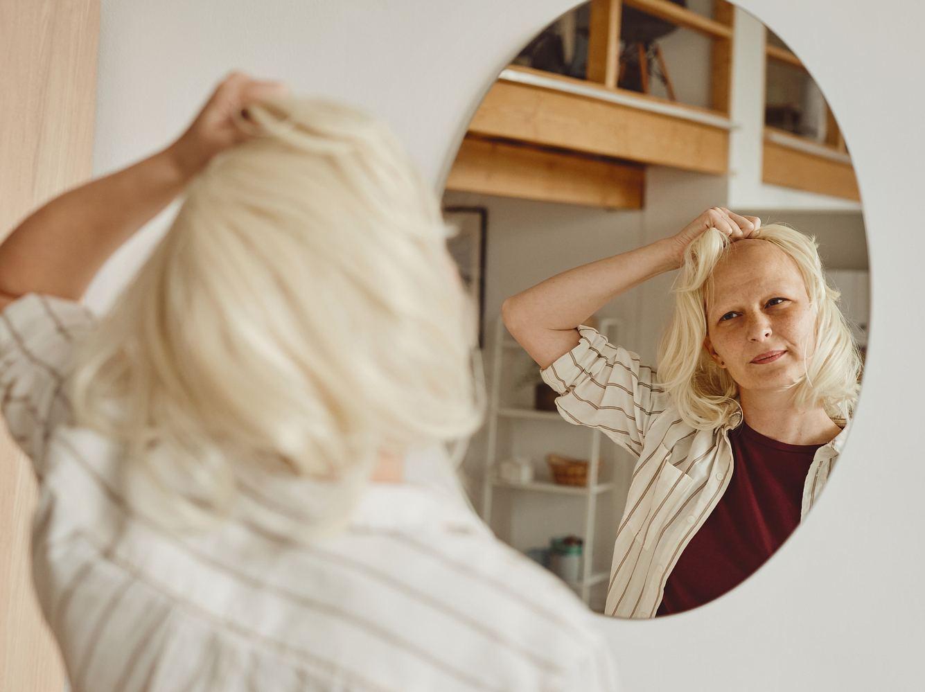 Krebspatienten mit Perücke vor einem Spiegel.