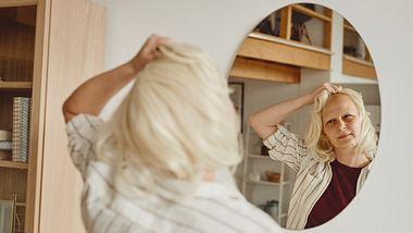 Krebspatienten mit Perücke vor einem Spiegel. - Foto: SeventyFour / iStock