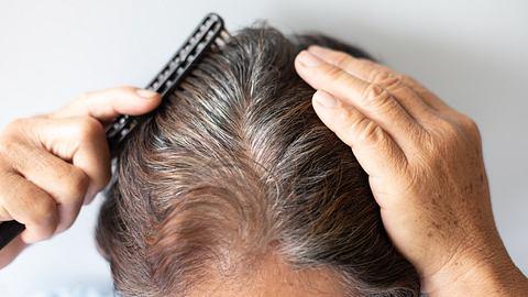 Frau kämmt sich die Haare.