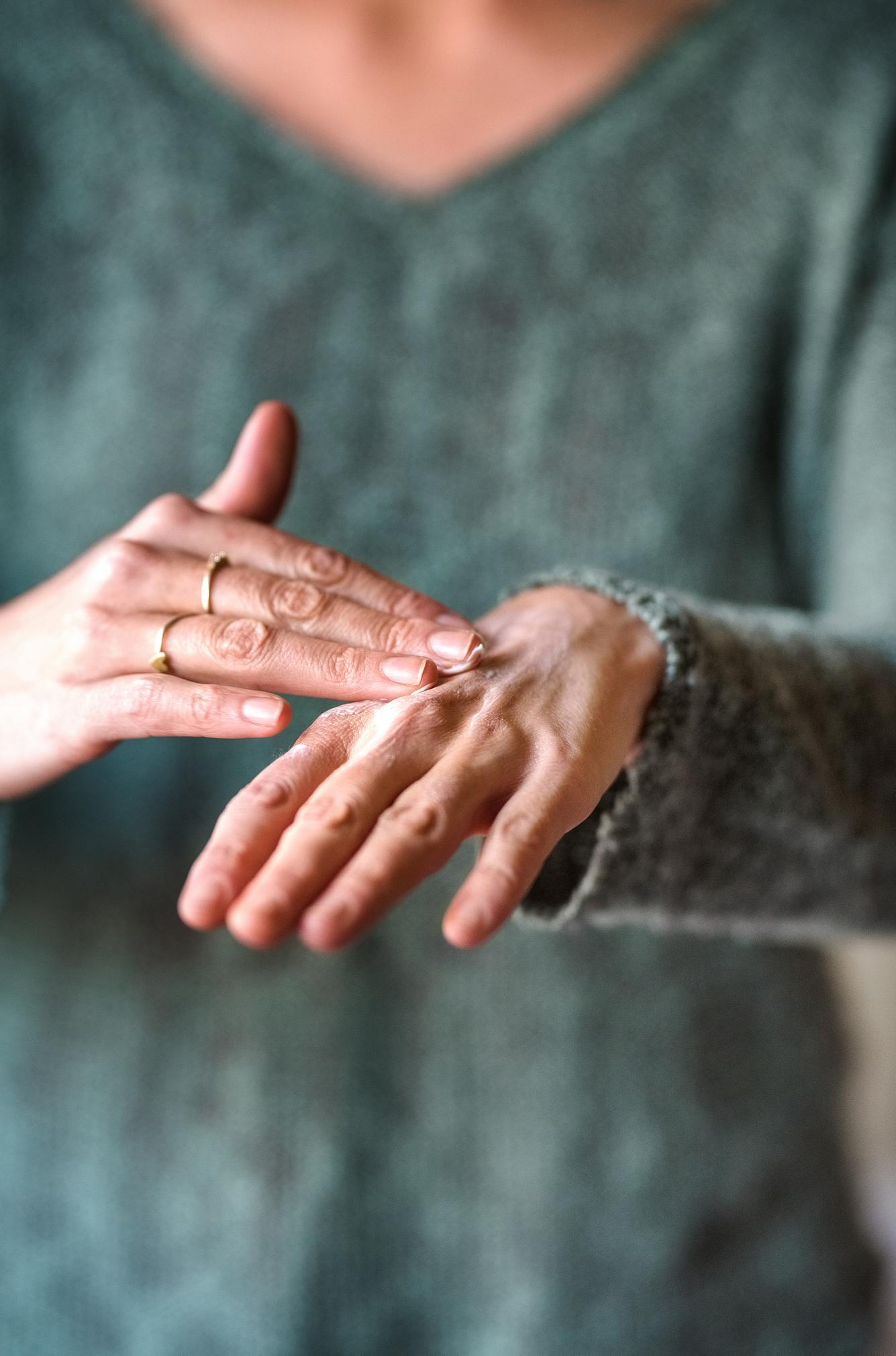Frau verwendet selbstgemachte Handcreme zum Eincremen.