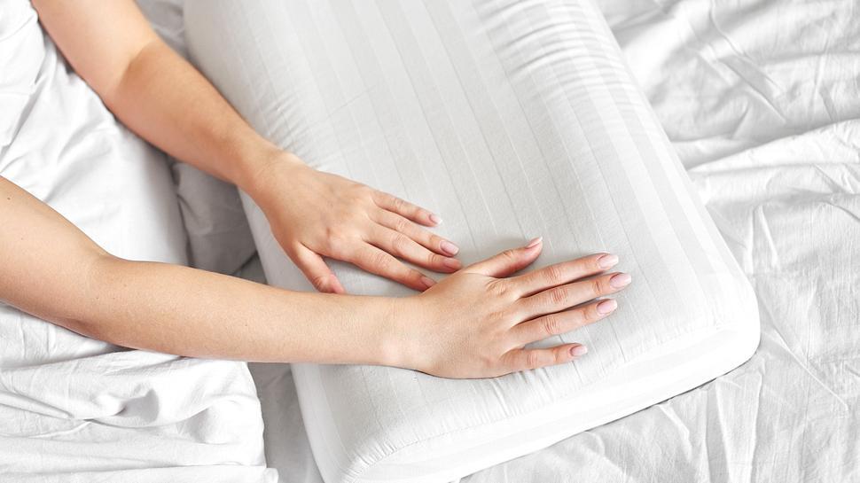 Weißes Heizkissen auf Bettlacken - Foto: iStock/amixstudio