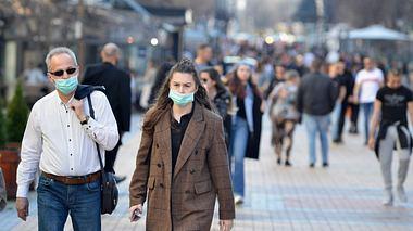 Passanten schützen sich mit einem Mund-Nasen-Schutz vor einer möglichen Ansteckung mit dem Coronavirus.  - Foto: iStock / JordanSimeonov