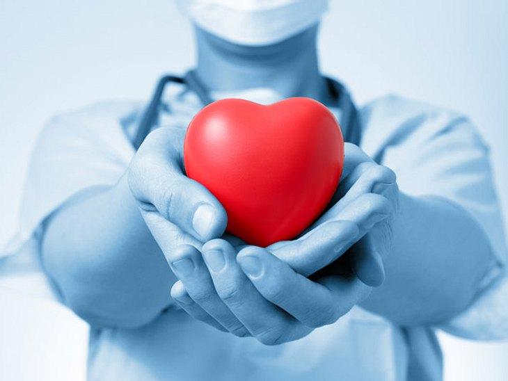Arzt hält Herz in der Hand Operation