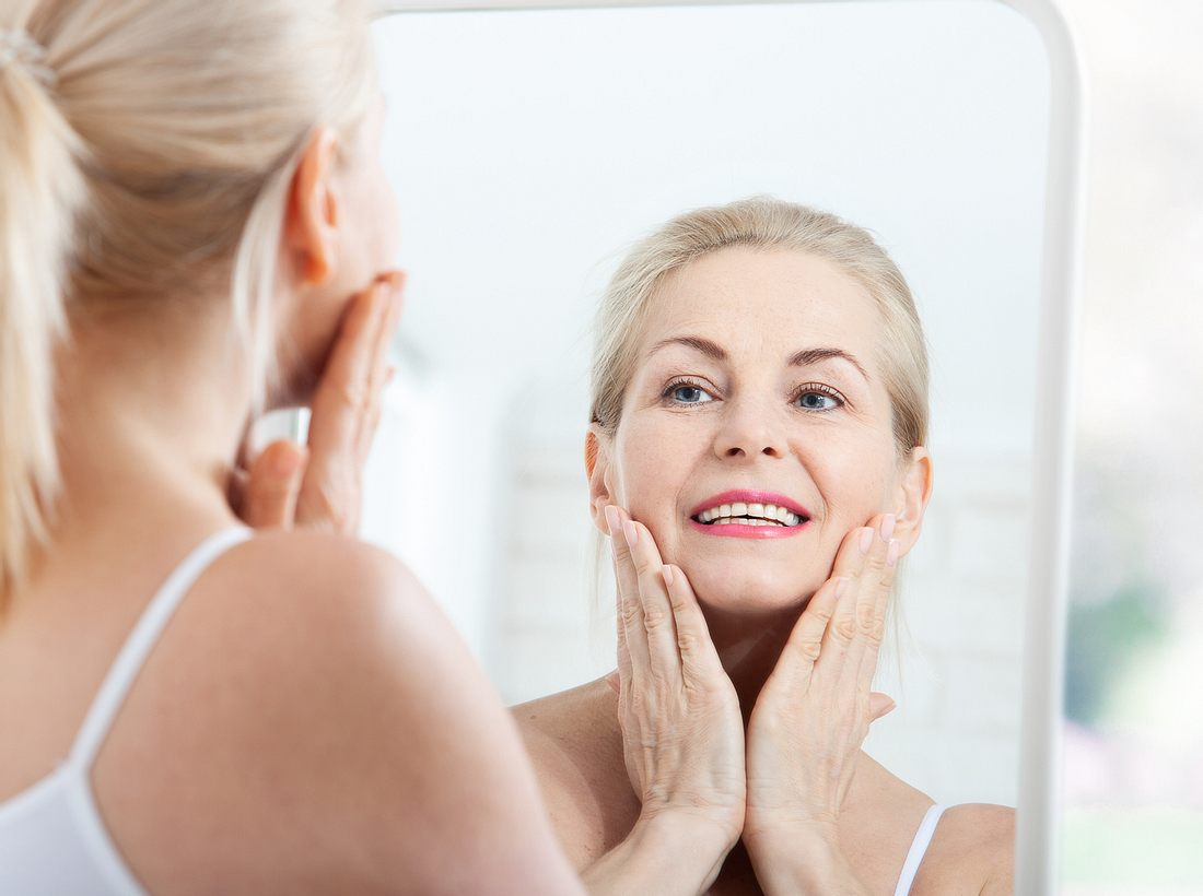 Frau verteilt Hyaluron-Creme in ihrem Gesicht
