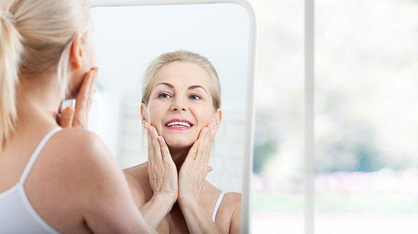 Frau verteilt Hyaluron-Creme in ihrem Gesicht - Foto: Victor_69 / iStock