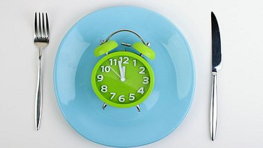 Ein Wecker liegt auf einem Teller.  - Foto: iStock