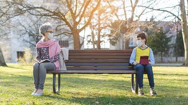 Eine Frau und ein Junge sitzen mit Abstand auf einer Parkbank. - Foto: iStock/ kzenon